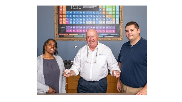 Polyonics CEO Jim Clemente presents Delilah Adams (lab technician / left) and Robert Guyette (chemist) with their patent awards, the company's first in its distinguished history.